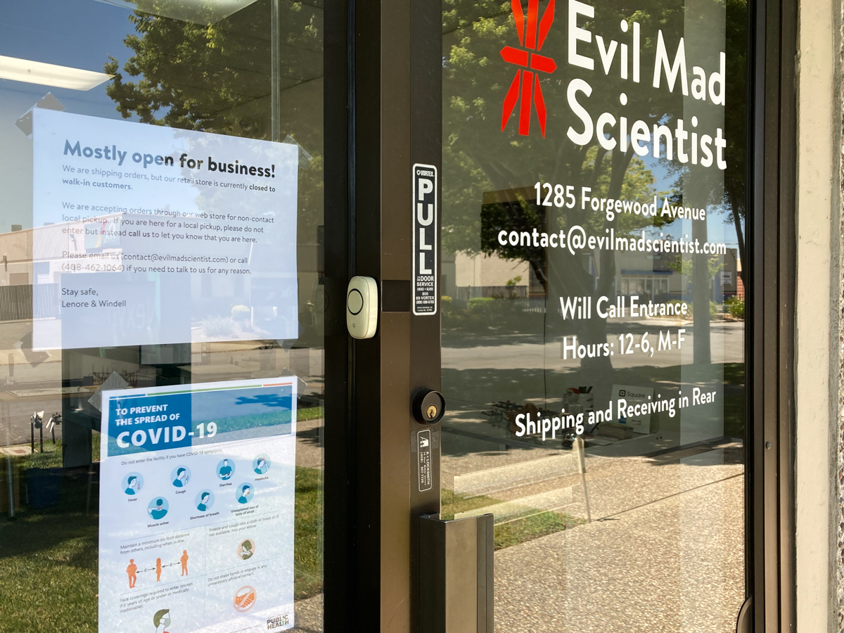 Evil Mad Scientist front door with signs about opening and COVID-19 requirements